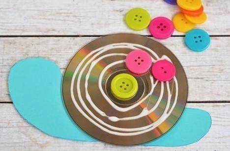 Поделка улитка с пуговицами Чтобы сделать такую поделку улитки с детьми 4-6 лет, понадобится картон, не нужный CD или DVD диск и разноцветные пуговицы.Вырезаем тело улитки из светлого картона.